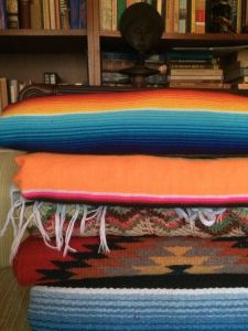 A stack of vintage textiles - runners, rugs, afghan and Saltillo blankets.
